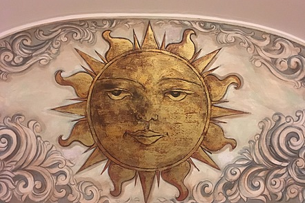 A medieval painting of the sun with a calm face