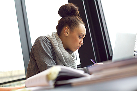 A woman taking notes as she studies.