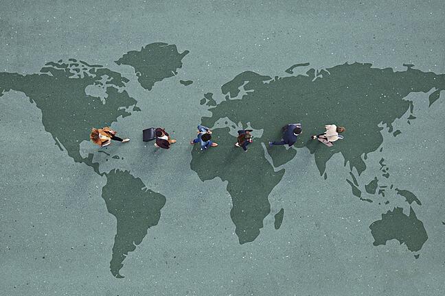 Businesspeople walking in line across world map.