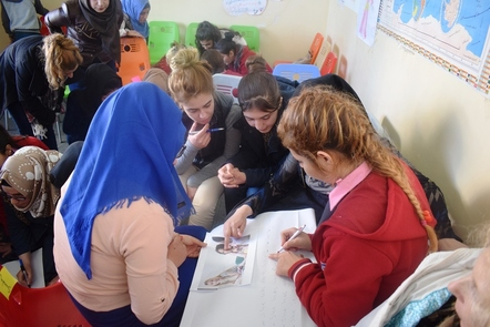 A group of young women sitting in groups in a classroom, working together