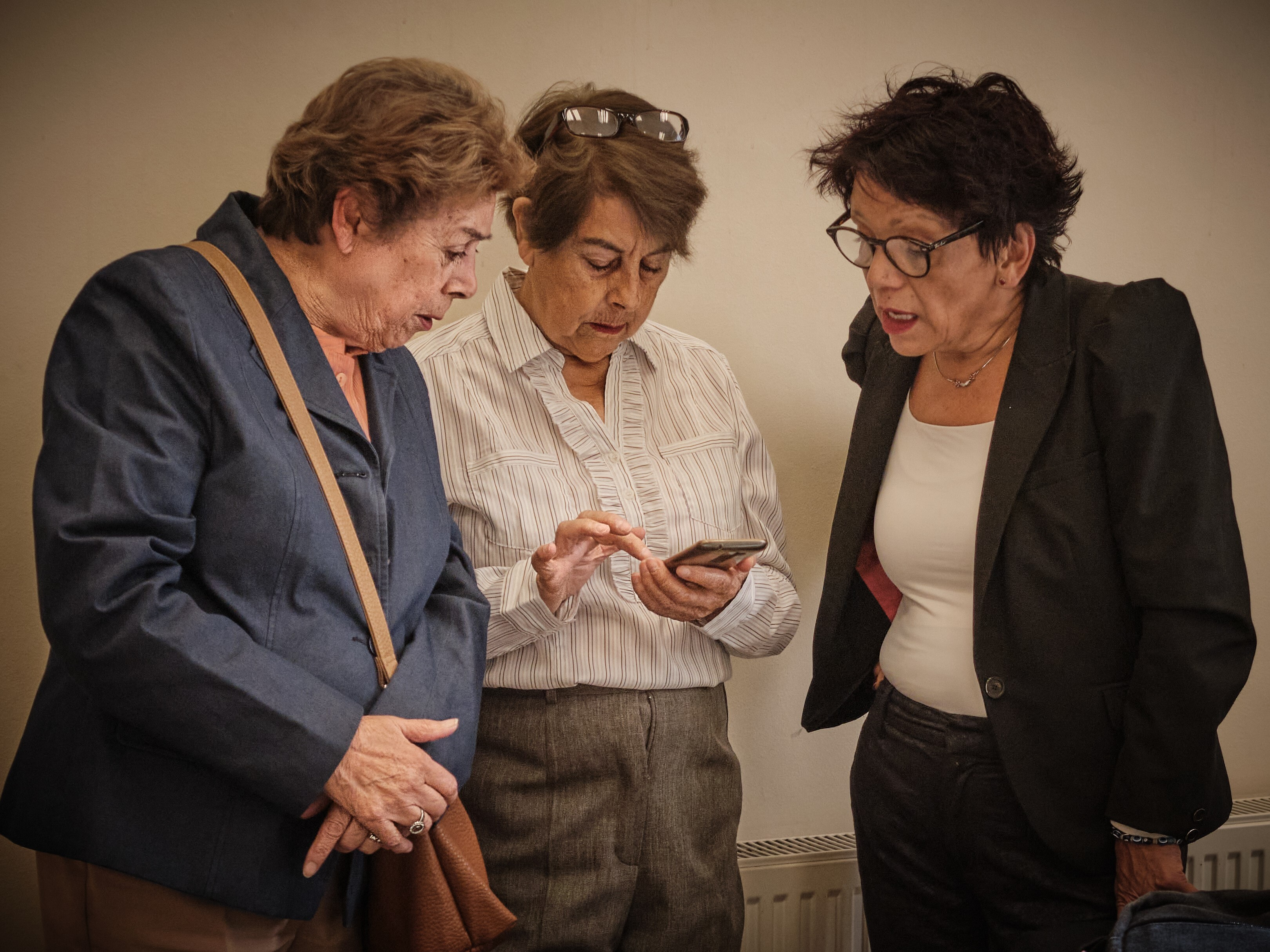 Three women dressed smartly, two in blazers and the middle one in a smart white shirt, are shown looking at a phone in a classroom in Santiago, Chile. They are all in their 50s or 60s.