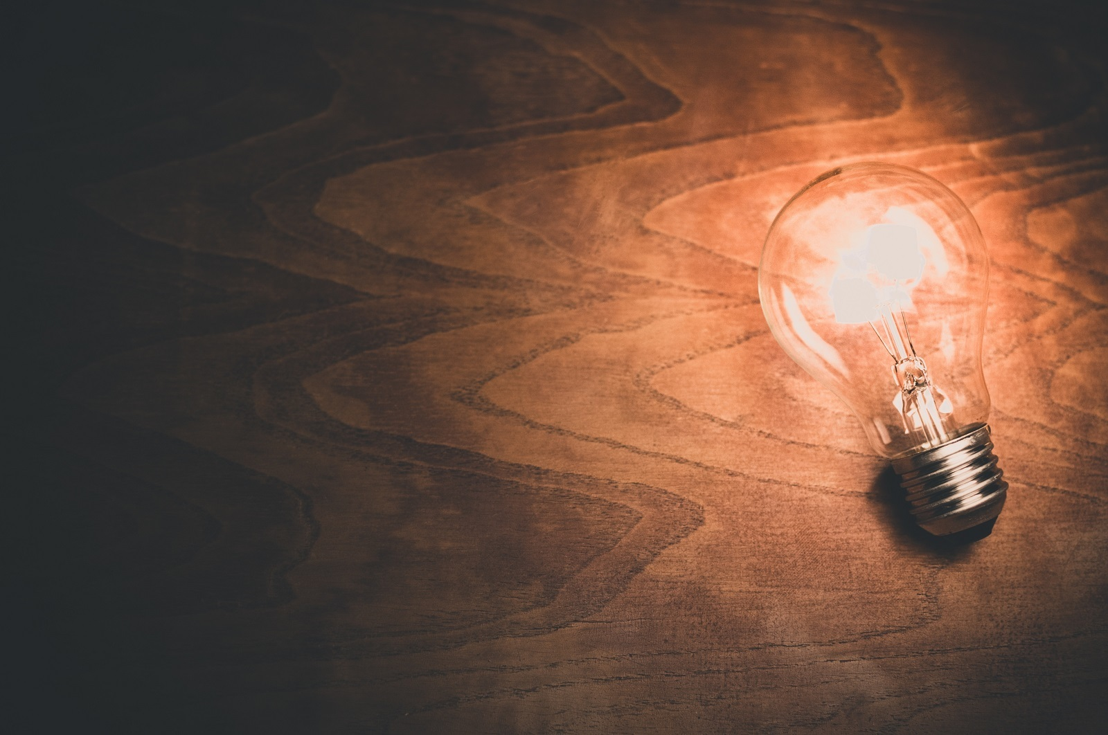 A light bulb on wooden background.