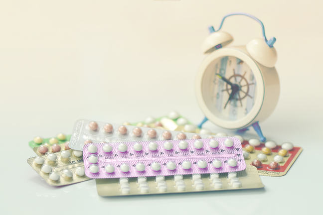 A selection of different tablets in original packaging beside a small alarm clock