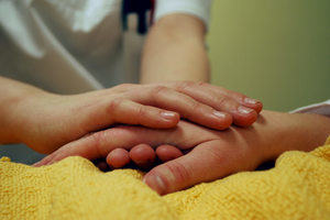 Two hands touching in a hospital bed