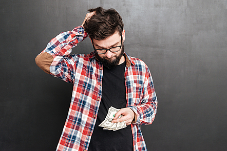 Photo of confused man dressed in shirt in a cage and wearing glasses standing over chalkboard while holding money