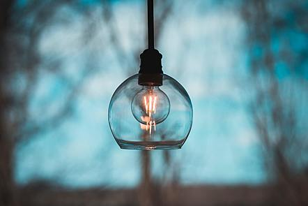 An image of a lit lightbulb in front of a blurred background of trees at early dusk.