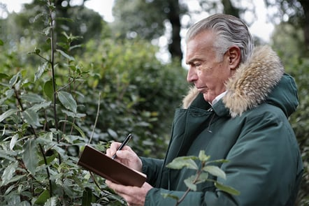 A man standing in a forest writing something down in his notebook.