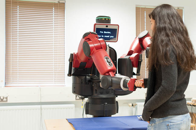A University of Reading student meeting a Baxter robot. She 'shakes' the robot's 'hand' and on the screen it says, 'I'm Baxter, nice to meet you'.