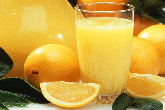 Glass or Orange Juice Alongside Oranges