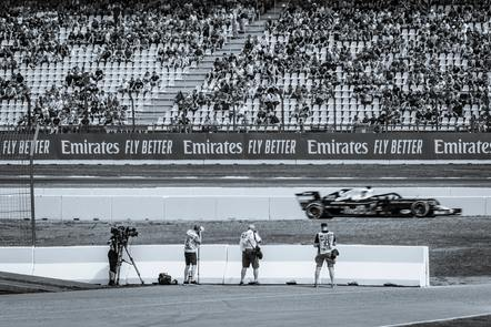 A camera crew on the sidelines of a F1 race, in black and white
