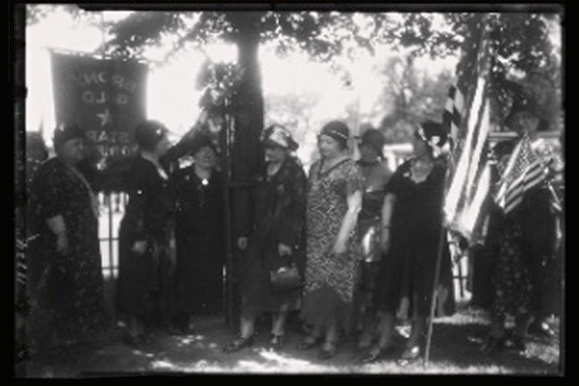 Old photograph showing a group of women with flags and banners