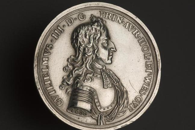 Silver medal showing in profile William III of Orange, with log flowing hair, wearing a breastplate of armour and knotted shirt collar with inscription to commemorate his landing at Torbay, 1688