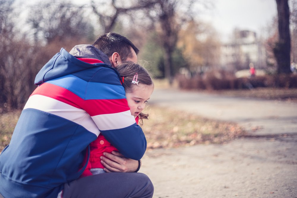 Father hugging his daughter in park