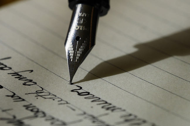 A black fountain pen is being used to write several words on a letter