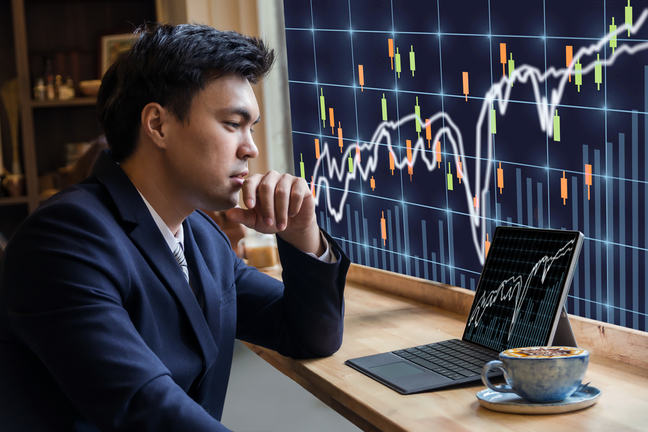 Man with coffee analysing data charts