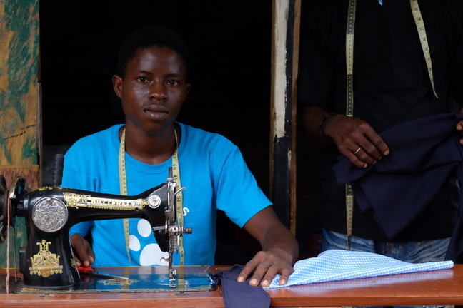 a young tailor looking straight at the camera sitting behind his sewing machine
