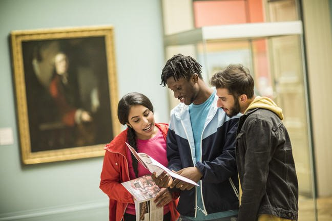 3 students standing in a museum looking at a booklet together