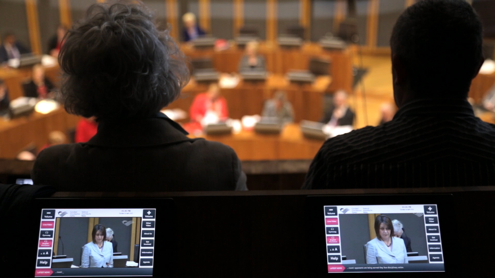 Two people sit in the chamber of the Welsh National Assembly watching politicians debate below.
