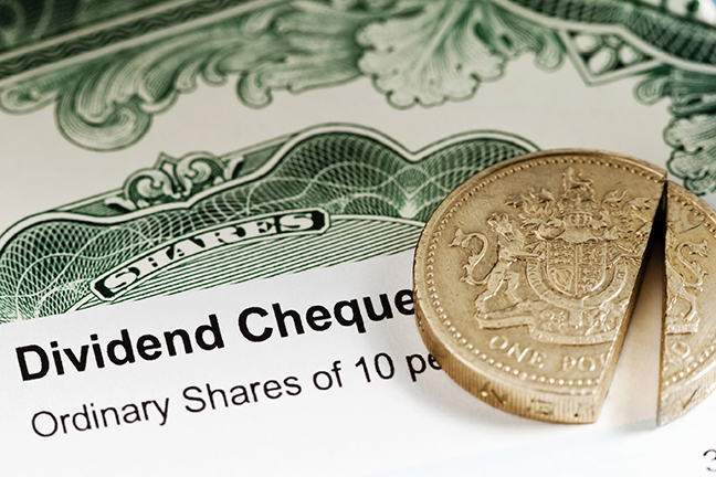 The image is of a UK share dividend with a  sliced pound coin laying on top of it.