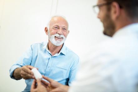 Happy senior man receiving a prescription medicine from doctor
