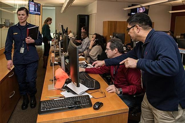 A team of 5 people sit along a desk lined with computers. One man is standing and gesturing towards the computer. A woman is also pictured walking and holding documents. These are support staff for the CDC's emergency operations center..