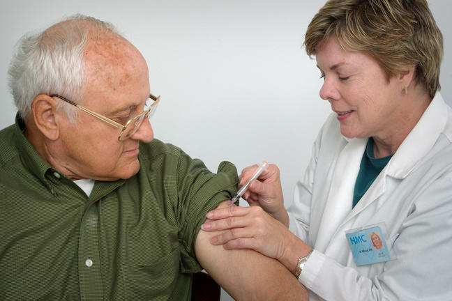 A nurse giving an older man a vaccination shot