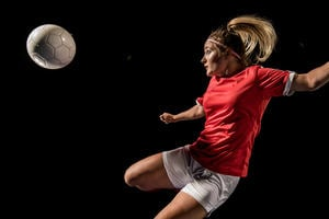 Female soccer player flying kick