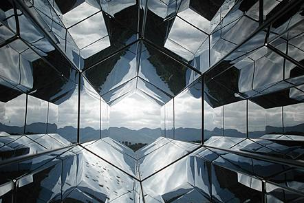 A view through a prismatic window to countryside beyond. The window appears to be made up of angled hexagons. all of the surrounding hexagonal panes simply distort and reflect one another's viewpoints to a degree that renders the image almost abstract.