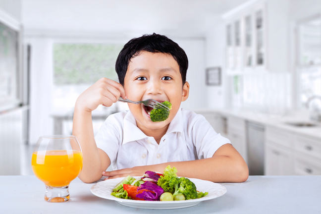 Young boy eating a plate of vegetables.