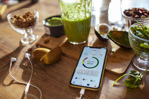 A mobile phone on a table surrounded by healthy foods