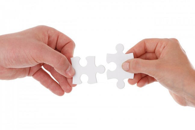 Two hands with two matching puzzle pieces