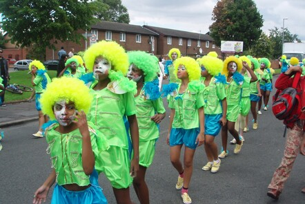 A photograph of children dancing in bright green outfits as part of the Manchester Carnival