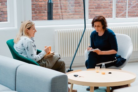 Two women meeting on chairs and writing notes