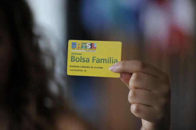 Woman's hand holding Bolsa Familia card