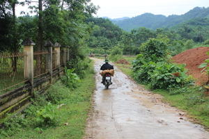 A narrow rural road in Vietnam with mud caked surface and puddles. A single motorbike with a sack tied to the back leaves a tyre track