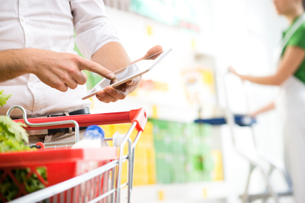 Person reviewing their shopping list in the supermarket.