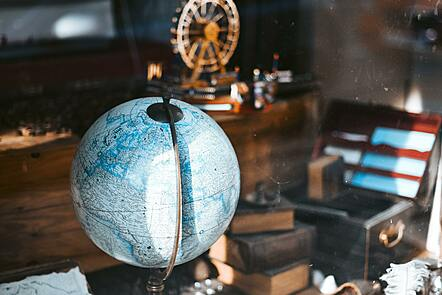 A globe on a wooden desk with glasses and paper scattered across the desk.
