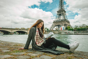 Girl reading poetry in front of the Eiffel Tower