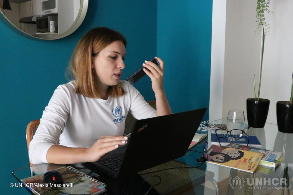 Woman wearing a UNHCR shirt sitting in front of a computer and talking on the phone
