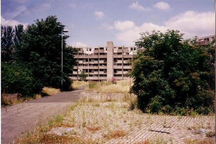 A photograph of the Hulme Crescents. The low rise apartment block sits behind an overgrown communal area
