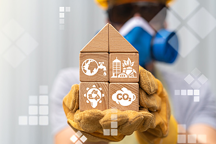 A man with a mask holding bricks that have the pictures related to circular economy on them.