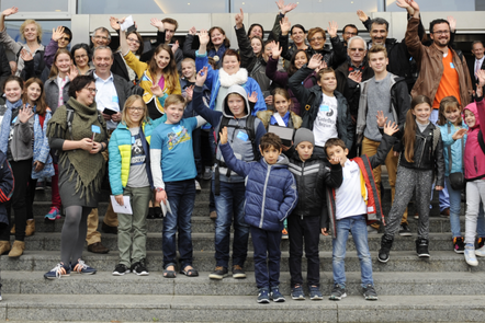A crowd of children, interspersed with a few adults, stand on a broad staircase outside a building, waiving at the camera.