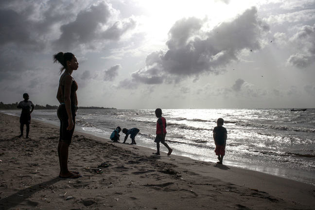 A teenage girl is singlet and shorts is standing on the beach facing the water with five younger children standing around her playing.