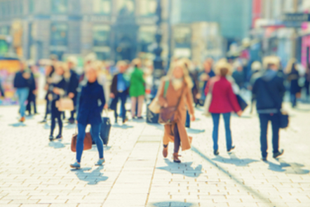 A collection of people walking on a crowded street.