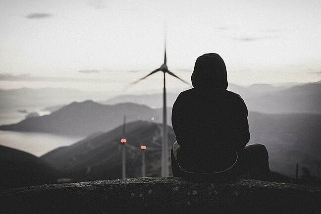 Photo of a person sitting on the edge of a building looking at a wind farm