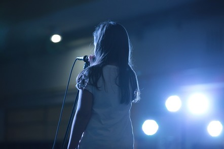A girl on a stage speaks into a microphone