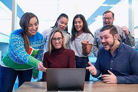 Six people around a laptop celebrating success.