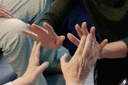 Image of two people's hands coming towards each other