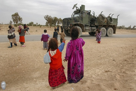 Najaf, Iraq. Children wave to an American convoy that passes on a local road.