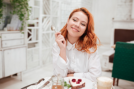 Image of young woman eating cake in cafe while drinking coffee